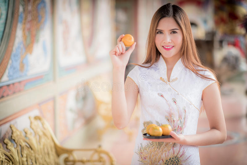 Asiatisk kinesisk kvinna i beträffande hållande orange lön för traditionell kines royaltyfri foto