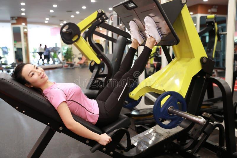 Asiatisk kinesisk kvinna i för ŒFitness för idrottshallï¼ utbildning för kvinna sport av benstyrka i idrottshallen arkivfoton