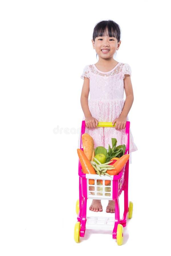 Asiatisk kinesisk liten flicka med shoppingspårvagnen mycket av vegetabl royaltyfria foton