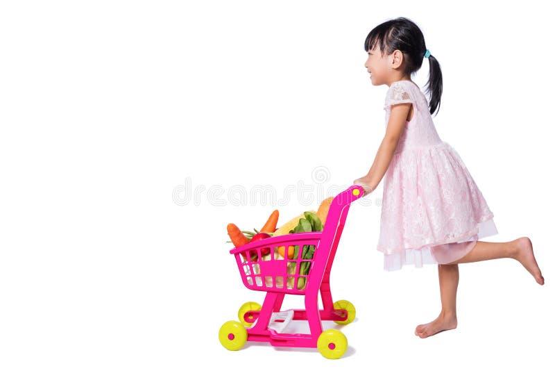 Asiatisk kinesisk liten flicka med shoppingspårvagnen mycket av vegetabl arkivfoto