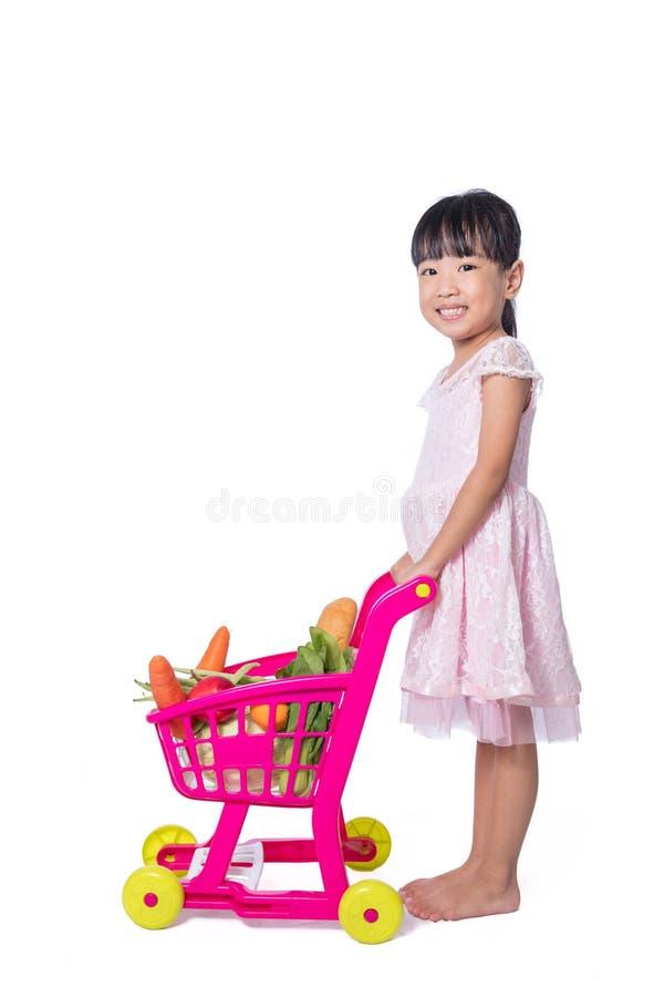 Asiatisk kinesisk liten flicka med shoppingspårvagnen mycket av vegetabl royaltyfri bild