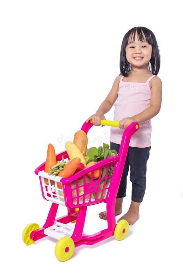 Asiatisk kinesisk liten flicka med shoppingspårvagnen mycket av vegetabl arkivfoton