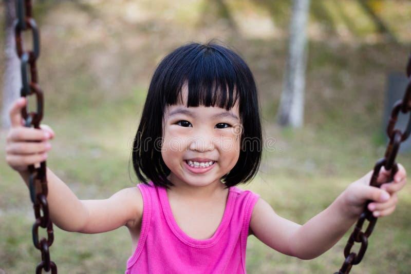 Asiatisk kinesisk liten flicka på gunga i lekplats royaltyfria foton