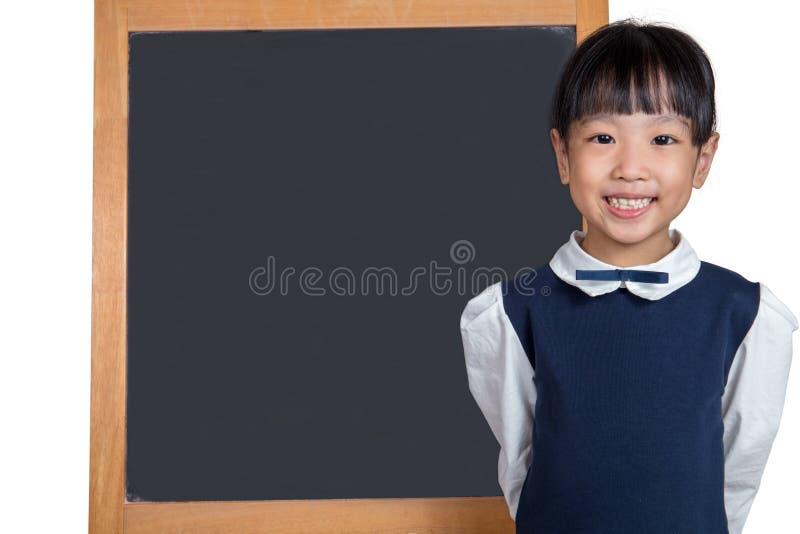 Asiatisk kinesisk liten flicka som framme står av svart tavla royaltyfri bild