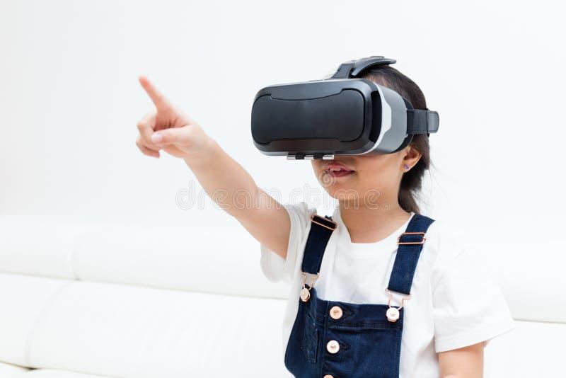 Asiatisk kinesisk liten flicka som hemma erfar virtuell verklighet royaltyfri foto