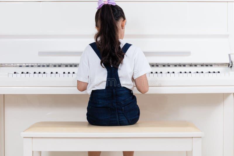 Asiatisk kinesisk liten flicka som hemma spelar det klassiska pianot royaltyfri fotografi