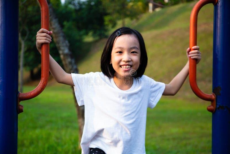 Asiatisk kinesisk liten flicka som leker utomhuslekplats royaltyfria bilder