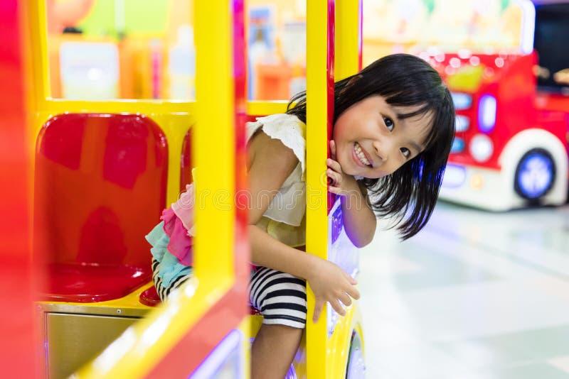 Asiatisk kinesisk liten flicka som rider Toy Bus arkivfoton