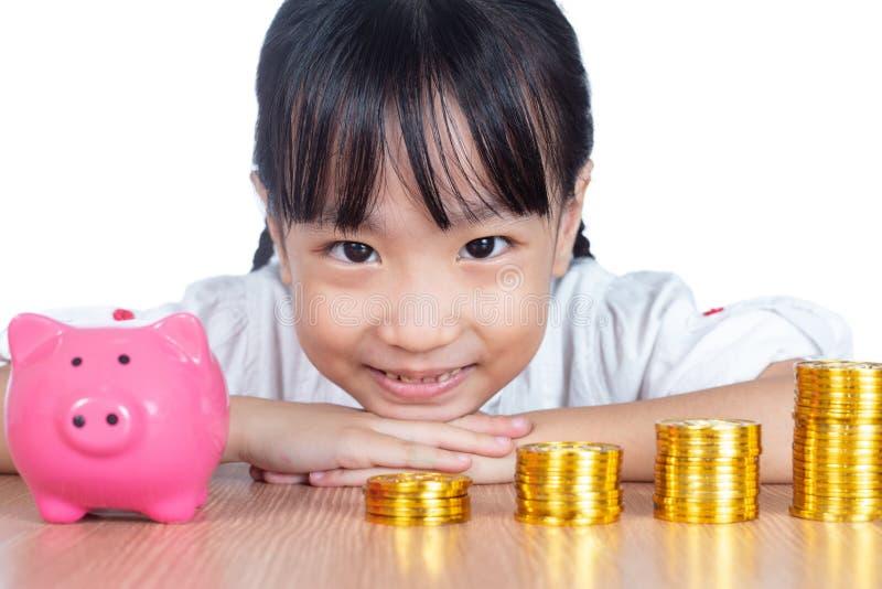Asiatisk kinesisk liten flicka som spelar med guld- Bitcoin royaltyfri foto
