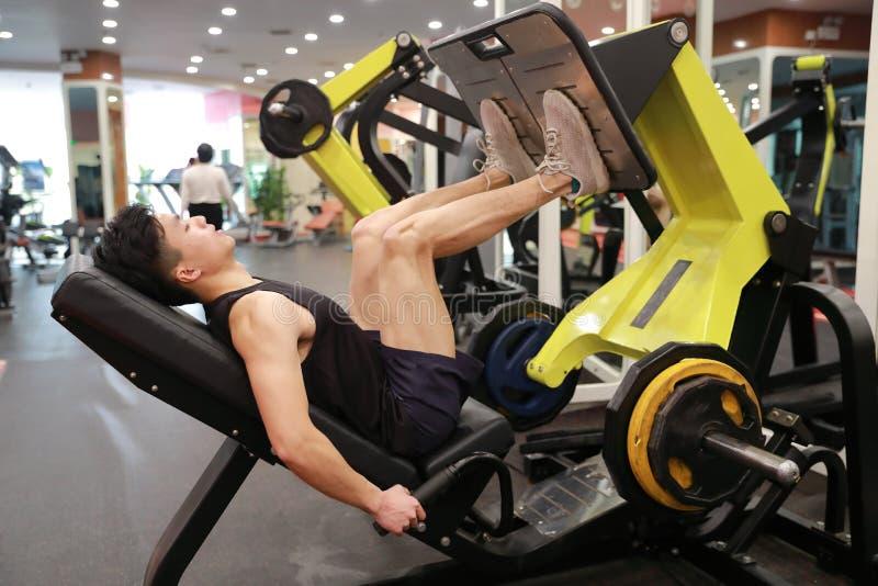 Asiatisk kinesisk man i för ŒFitness för idrottshallï¼ utbildning för man sport av benstyrka i idrottshallen royaltyfria foton