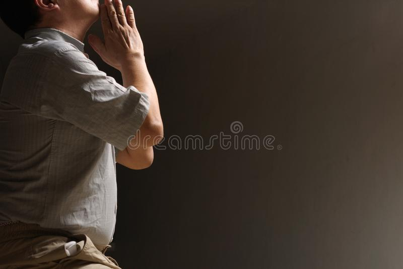 Asiatisk kinesisk man som ber ensam i mörkret royaltyfri fotografi