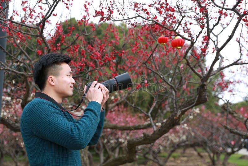 Asiatisk kinesisk manfotograf i natur arkivbild