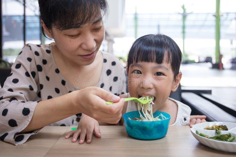 Asiatisk kinesisk moder och dotter som äter nötköttnudlar arkivfoto