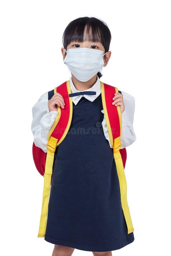 Asiatisk kinesisk skolaflicka med skolapåsen och den bärande maskeringen arkivfoton