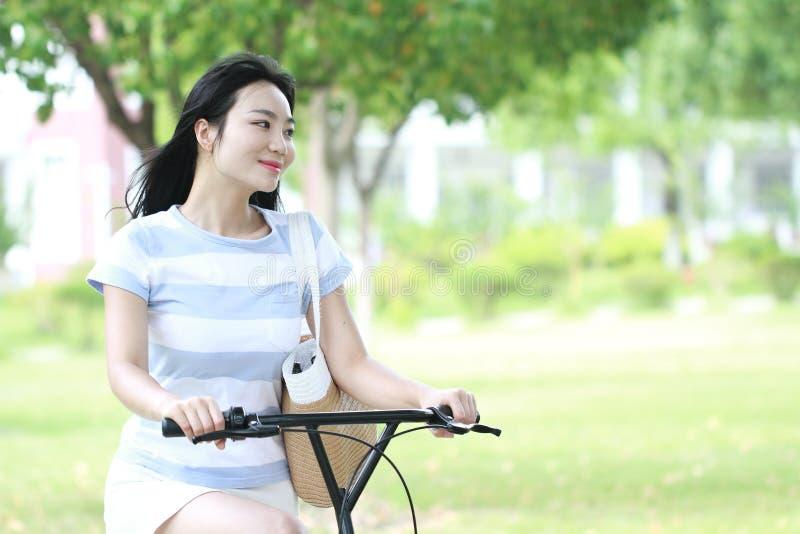 Asiatisk kinesisk ung härlig, elegantly klädd kvinna med att dela cykeln Skönhet, mode och livsstil arkivfoto