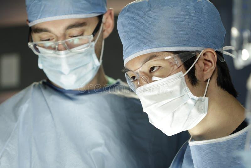 Asiatisk kirurg som arbetar med assistenten i kirurgi royaltyfri bild