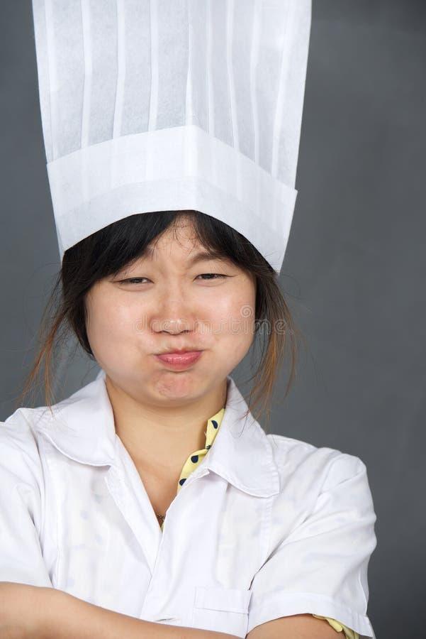 Asiatisk kock i högväxt toque arkivfoton