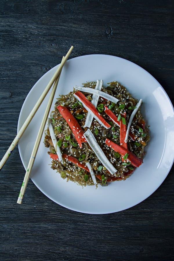 asiatisk kokkonst Fenchoza sallad som stekas med gr?nsaker som dekoreras med gr?splaner och krabbapinnar Riktig n?ring sund mat B fotografering för bildbyråer