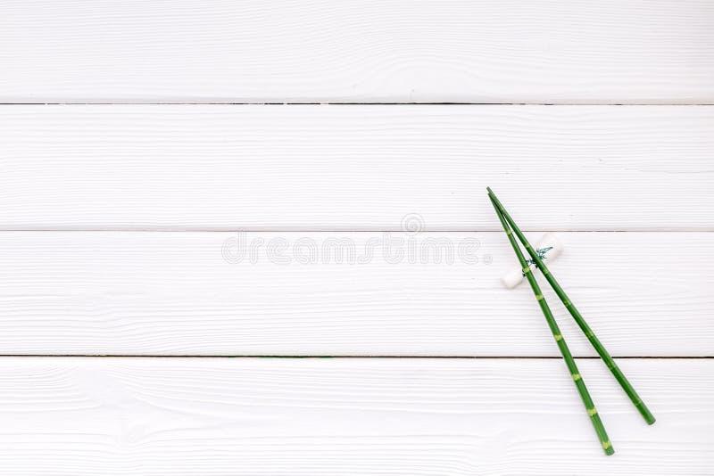 Asiatisk kokkonstuppsättning med bambupinnar för sushi och maki på vit träåtlöje för bästa sikt för bakgrund upp royaltyfria foton