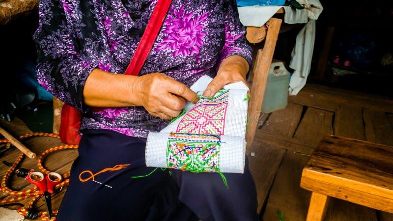 Asiatisk kullestamkvinna som broderar traditionell hemslöjd royaltyfri fotografi