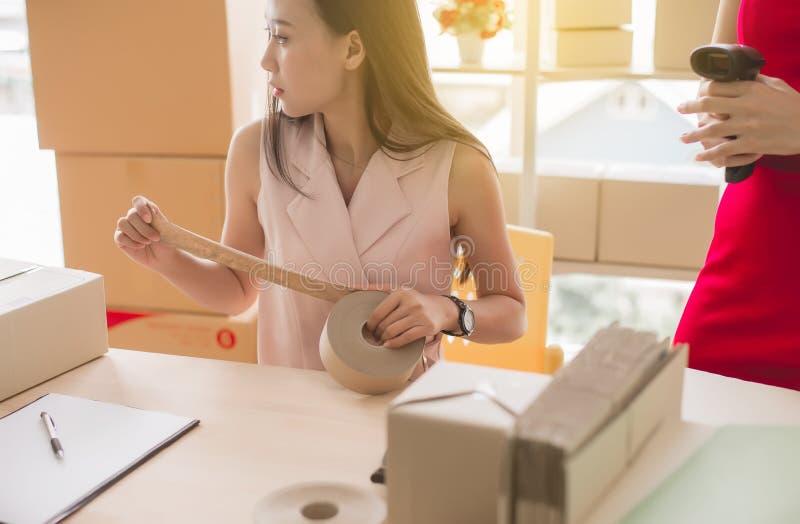 Asiatisk kvinnaägare som använder den förpackande produkten för tejp och arbetar det hemmastadda kontoret, online-små och medelst royaltyfria bilder