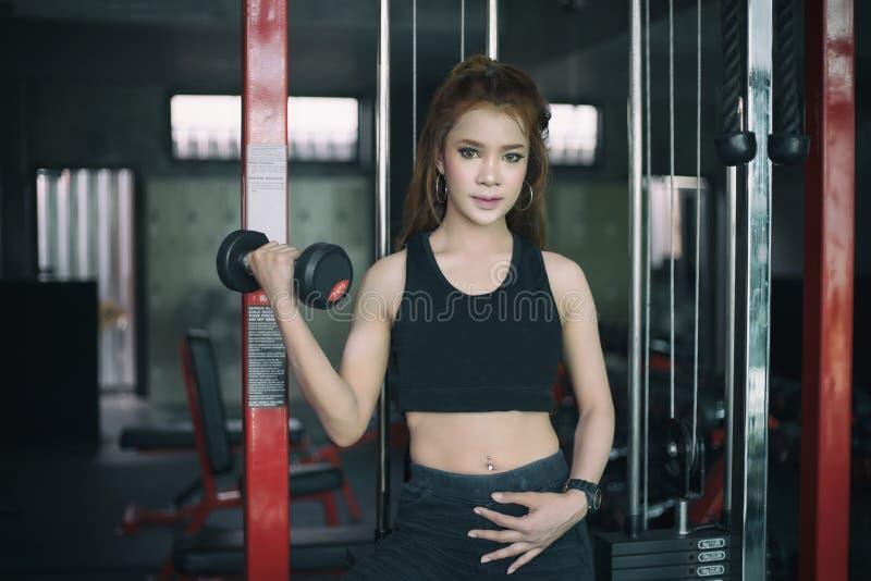 Asiatisk kvinnaövning för ung kondition med maskinkabelövergång royaltyfri fotografi