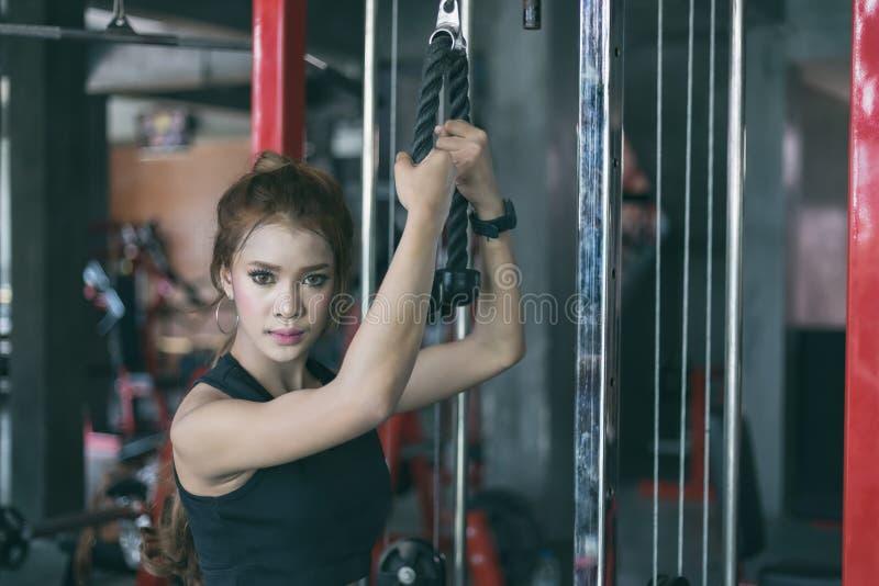 Asiatisk kvinnaövning för ung kondition med maskinkabelövergång fotografering för bildbyråer