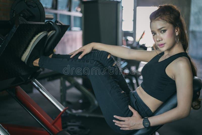 Asiatisk kvinnaövning för ung kondition med maskinkabelövergång arkivfoto