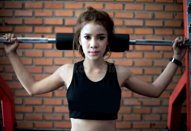 Asiatisk kvinnaövning för ung kondition med maskinkabelövergång royaltyfria foton