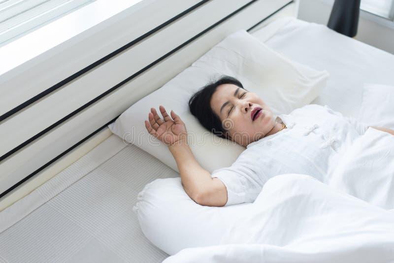 Asiatisk kvinna för äldre person som snarkar, därför att tack vare trött av arbete, kvinnlig snor, medan sova på säng arkivbilder