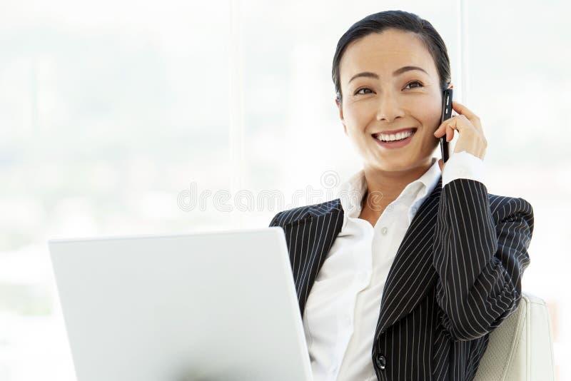 Asiatisk kvinna för affärsledare med bärbara datorn och smartphonen arkivfoto