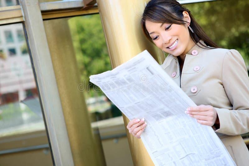 asiatisk kvinna för avläsning för affärstidning royaltyfria bilder