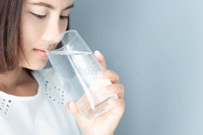 Asiatisk kvinna för Closeup som dricker rent vatten med grå bakgrund, hälsovårdbegrepp, selektiv fokus arkivbilder