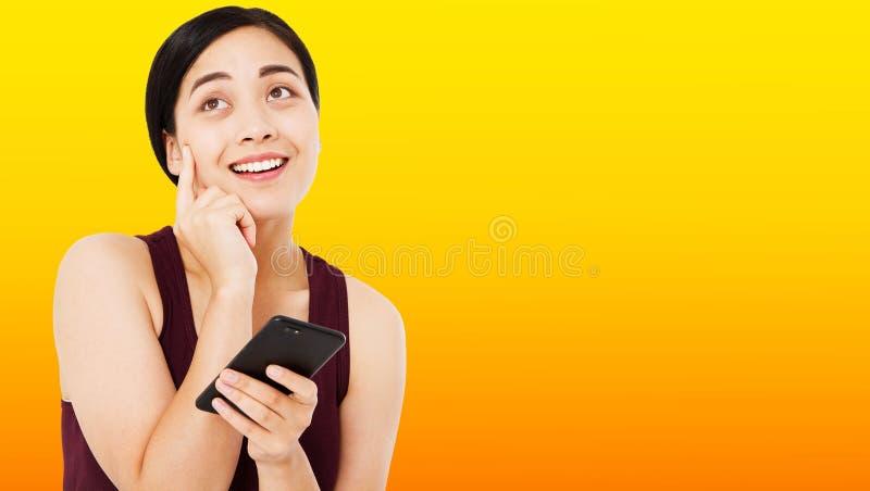 Asiatisk kvinna för emotionell brunett på orange bakgrund, lycklig korean arkivfoton