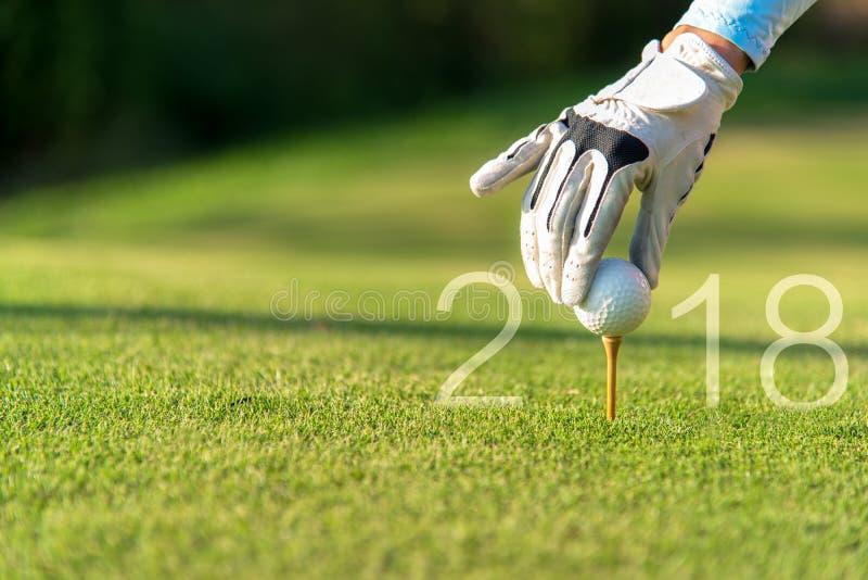 Asiatisk kvinna för golfare som sätter golfboll för det lyckliga nya året 2018 på den gröna golfen, kopieringsutrymme arkivfoto