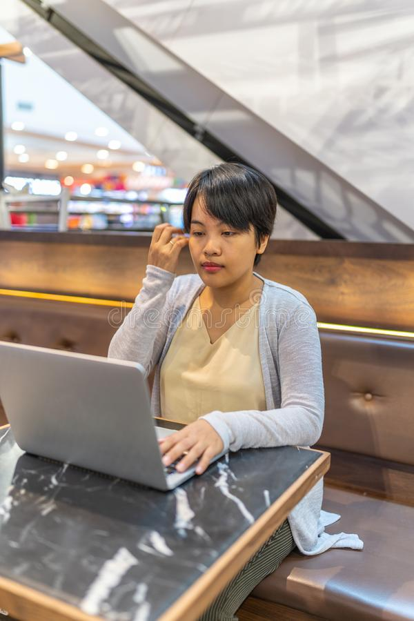 Asiatisk kvinna för kort hår som arbetar på bärbara datorn på kaffetabellen arkivbild