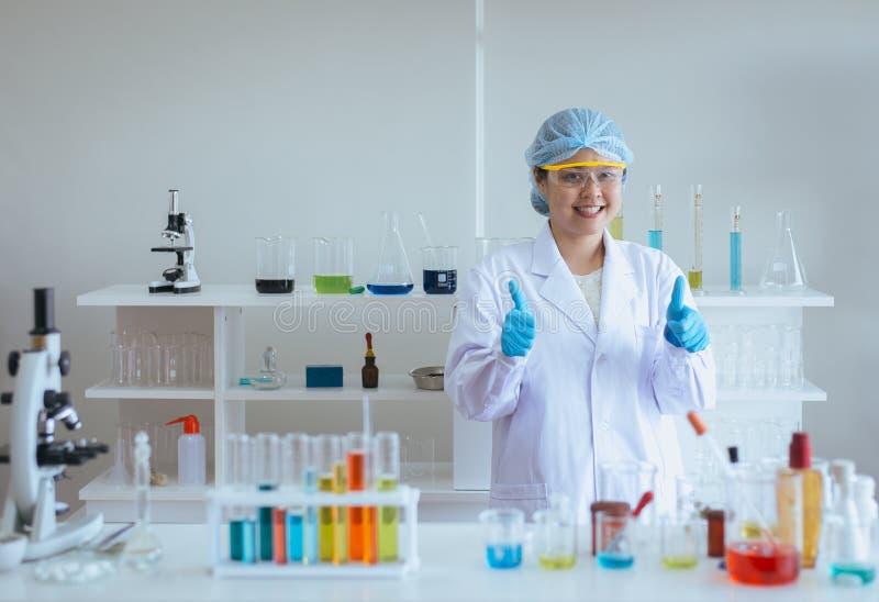 Asiatisk kvinna för lycklig forskare som studerar medicinska kemikalieer och visar tummen upp i laboratorium arkivbild