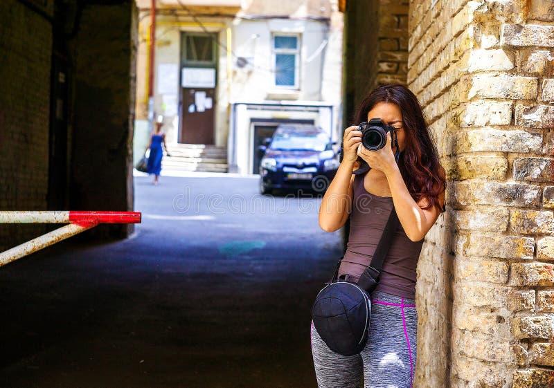Asiatisk kvinna för lycklig härlig handelsresande med kameran Unga glade asiatiska kvinnor som anv?nder kameran till framst?llnin royaltyfria bilder