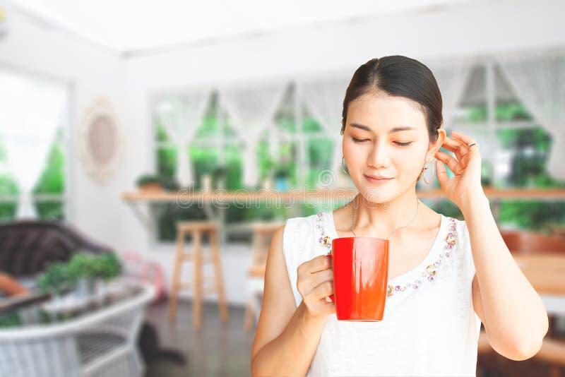 Asiatisk kvinna för skönhet som dricker kaffe med det suddiga hemtrevliga stilkafét royaltyfri bild