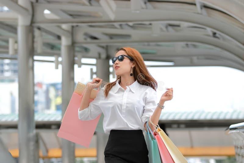 Asiatisk kvinna för skönhet som rymmer färgrika shoppingpåsar Innehåll lutning- och urklippmaskeringen royaltyfria bilder
