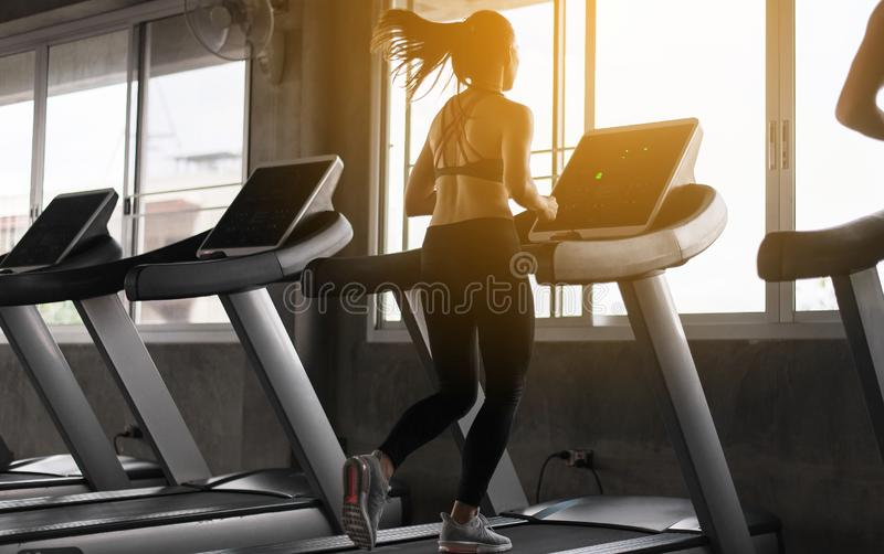 Asiatisk kvinna för sport som kör på trampkvarnar som gör cardio utbildning, arg färdig kropp och muskulöst i idrottshallen, tona arkivfoto