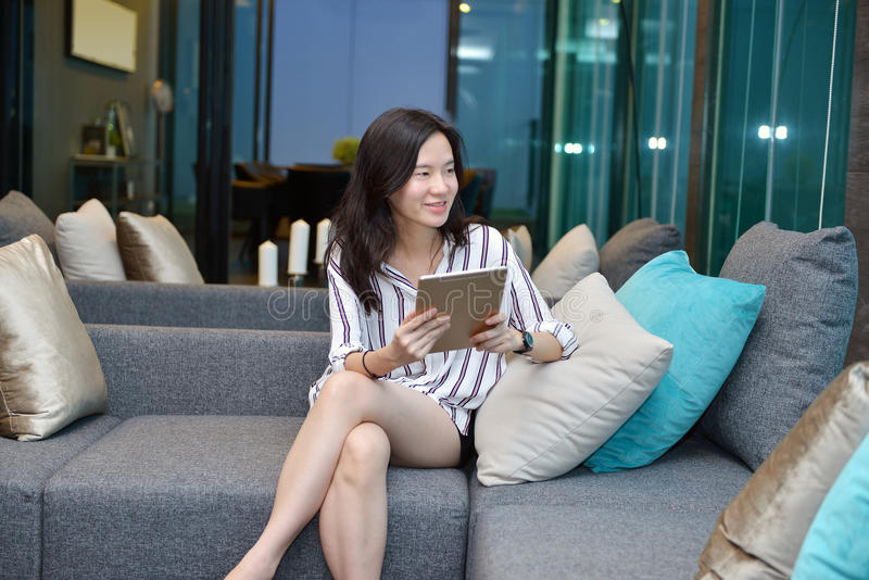 Asiatisk kvinna för tillfällig affär som använder en minnestavla på soffan i bosatt roo fotografering för bildbyråer