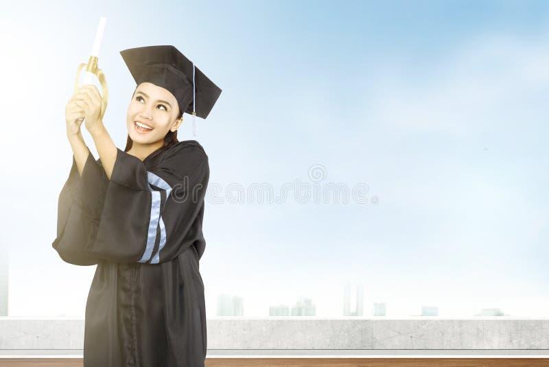 Asiatisk kvinna i akademikerm?ssahatt och diplom som avl?gger examen fr?n h?gskolan royaltyfri bild