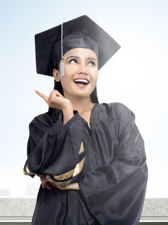 Asiatisk kvinna i akademikerm?ssahatt som avl?gger examen fr?n h?gskolan royaltyfri fotografi