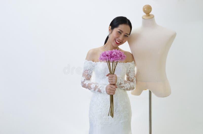 Asiatisk kvinna i bröllopsklänning med den manliga skyltdockan 1 royaltyfria foton