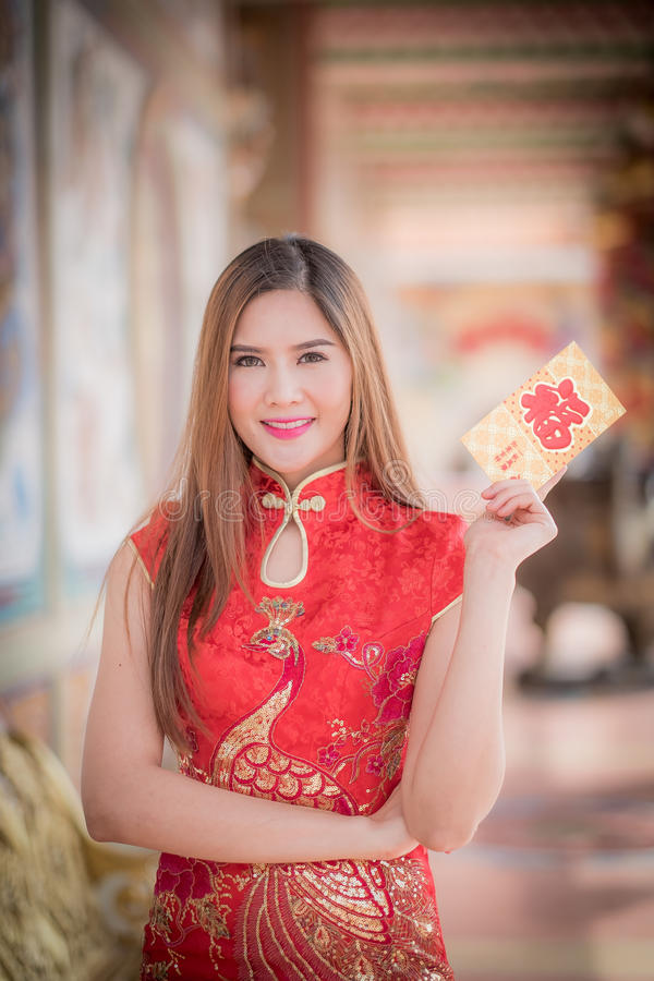 Asiatisk kvinna i 'den lyckliga' hållande rimmat verspar för kinesisk klänning (kines w arkivfoto