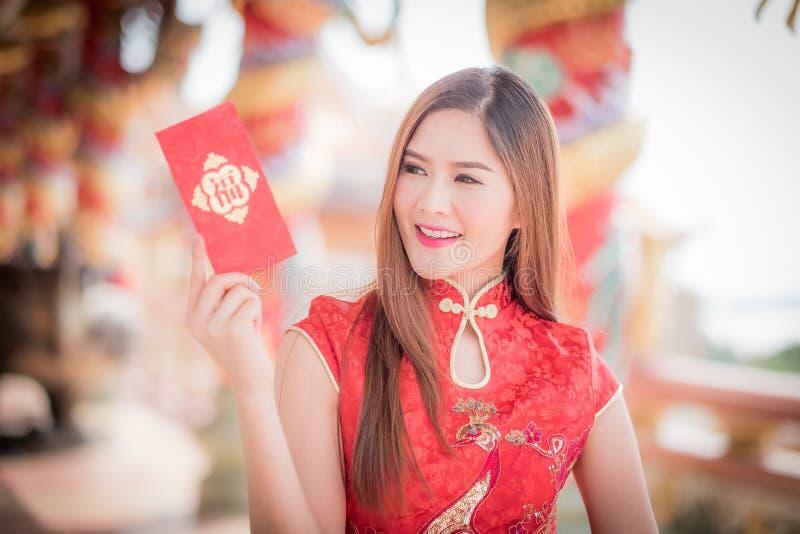 Asiatisk kvinna i 'den lyckliga' hållande rimmat verspar för kinesisk klänning (kines w royaltyfri fotografi