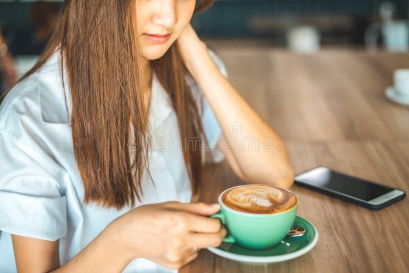 Asiatisk kvinna i ett kaf? som dricker kaffe Stående av den asiatiska kvinnan som ler i signal för färg för coffee shopkafétappni arkivfoto