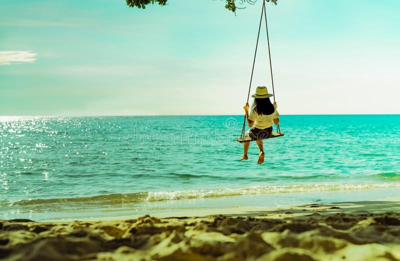Asiatisk kvinna i för kläderhatt för tillfällig stil gunga gungorna på stranden och att se för sand det härliga tropiska paradish fotografering för bildbyråer