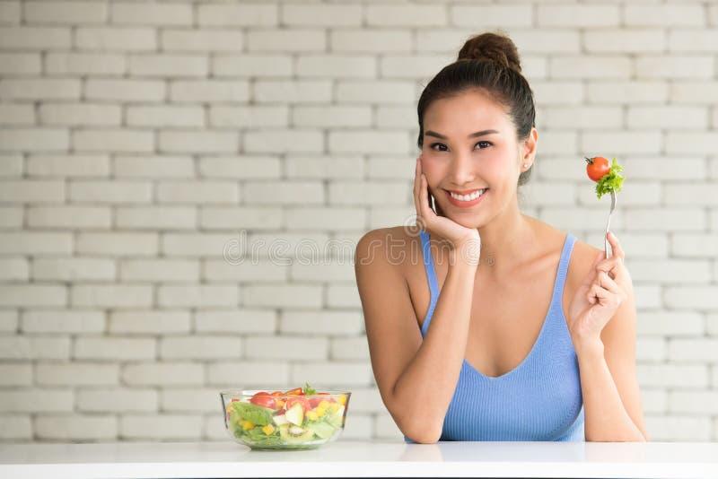 Asiatisk kvinna i glade ställingar med salladbunken på sidan royaltyfri foto
